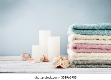 Stack of  towels with candles and shells on light blue background