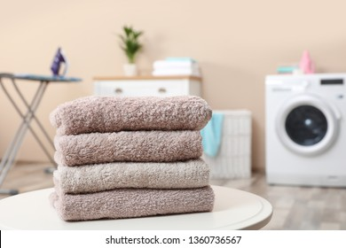 Stack of towels on table against blurred background, space for text
