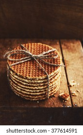 Stack of traditional dutch caramel waffles tied up with jute twine on rustic wooden background