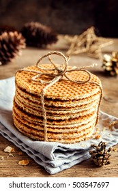 Stack of traditional dutch caramel waffles tied up with jute twine on rustic wooden background with Christmas decor - homemade Christmas pastry