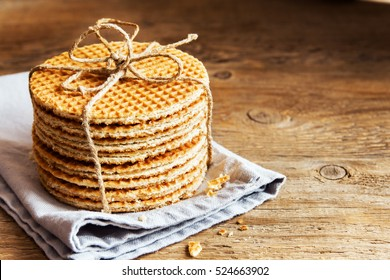 Stack of traditional dutch caramel waffles tied up with jute twine on rustic wooden background, copy space, selective focus