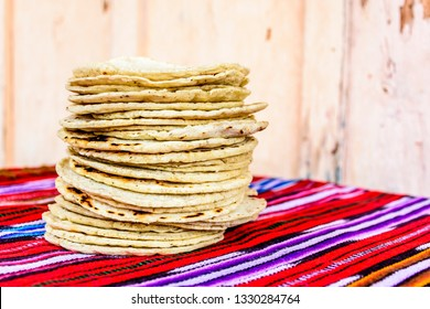 Stack of traditional handmade Guatemalan corn tortillas a staple food in Guatemala on red striped handwoven tablecloth