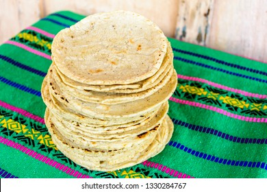 Stack of traditional handmade Guatemalan corn tortillas a staple food in Guatemala on green striped handwoven tablecloth