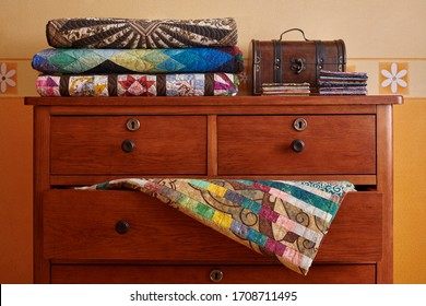 Stack of traditional quilts and wooden chest on chest of drawers