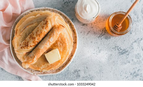 Stack of traditional russian pancakes blini on gray background with copy space. Homemade russian thin pancakes blini. Russian food, russian kitchen. Top view or flat lay