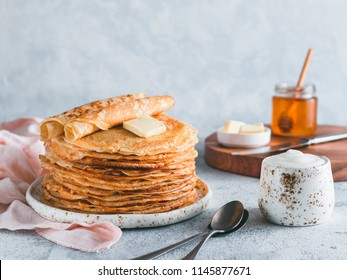 Stack of traditional russian pancakes blini on gray background with copy space. Homemade russian thin pancakes blini. Russian food, russian kitchen
