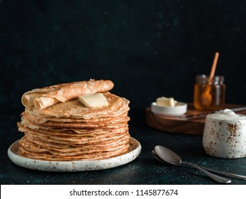 Stack of traditional russian pancakes blini on black background with copy space. Homemade russian thin pancakes blini. Russian food, russian kitchen