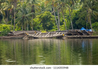 Stack of traditional, wooden canoes on the shores of Kannur backwaters, Kerala, India.