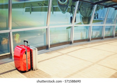 stack of traveling luggage in airport terminal and passenger plane flying over building in city
