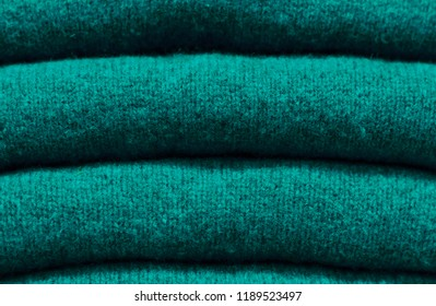 Stack of trend Quetzal Green woolen sweaters close-up, texture, background