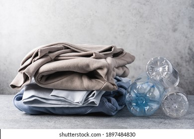 Stack of trendy modern clothes made from recycled plastic. Eco products and zero waste concept