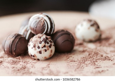 Stack of truffles on a wooden table covered with cocoa powder