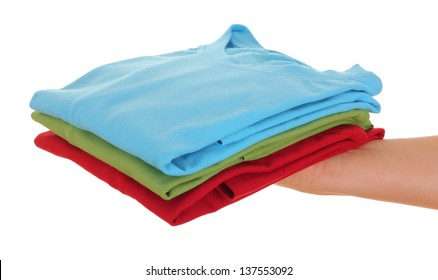 stack of t-shirt on women hand, over white background