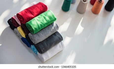 stack of t-shirts rolled up on white table