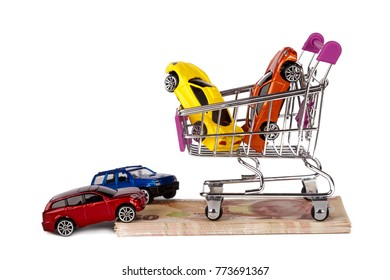 Stack of Turkish Lira banknotes with shopping cart and colorful toy cars in money consuming concept, isolated on white background.