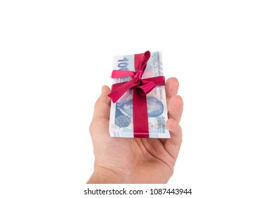 Stack of Turkish lira banknotes wrapped with ribbon as a gift on hand, isolated on white background.