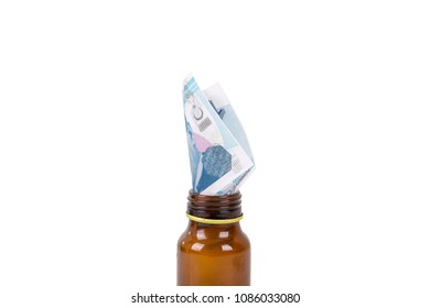 Stack of Turkish liras banknotes inside and medicine pills bottle with the meaning of health and medicine expensiveness, isolated on white background.