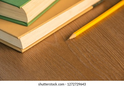 stack of two aged books sitting on a wooden brown table with yellow pencil