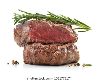 stack of two juicy grilled beef fillet steaks with rosemary isolated on white background, selective focus