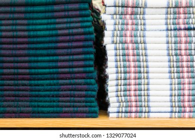 Stack of two types folded woolen tartan checkered plaids or scarves lying on a shelf.