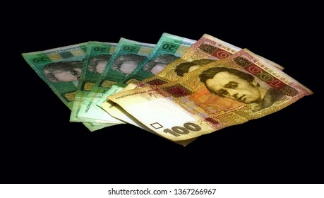 a stack of Ukrainian banknotes in denominations of 100 and 20 hryvnas isolated on a black background, fan view