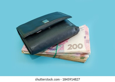 stack with Ukrainian hryvnia and black men's wallet on a blue background. Close-up.