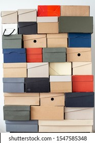 Stack of unevenly folded shoe boxes against a white wall. Seasonal sales and discounts. Vertical photo.