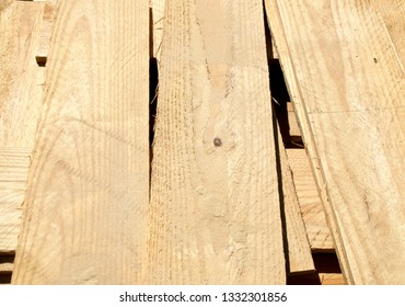 A stack of unfinished pine wood planks outdoors in sunlight.