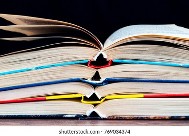 a stack of unfolded books on a black background