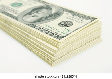 A stack of US dollars on a white plane.