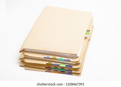 A stack of used folders in color-coded numbers and tabs containing paper documents.