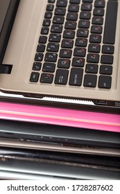Stack of used laptops in different colors and models. Tha notebooks for repair and service.