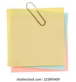 Stack of varicoloured memos with silver paper clip on a pure white background. Waiting for your message.