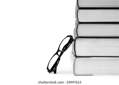 Stack of various books and glasses on white background