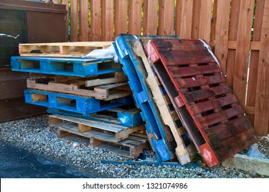 A stack of various colored forklift pallets or skids are stacked outdoors near dumpster and fence.