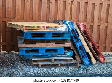 A stack of various colored forklift pallets or skids are stacked outdoors against fence.