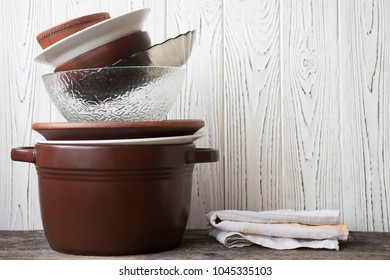 Stack of various crockery and kitchen towel on rustic wooden table. Plates, dish, bowls and mugs.
