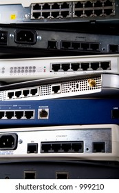 A stack of various network devices including DSL modems, routers, hubs and switches.