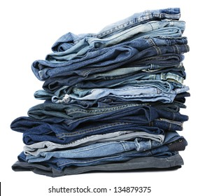 A stack of various pairs of jeans pants isolated on white background.