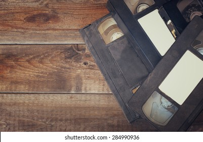 stack of VHS video tape cassette over wooden background. top view photo