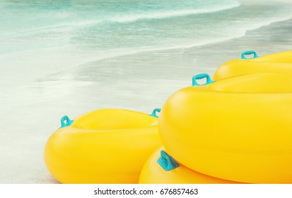 Stack of vibrant yellow Inflatable tubes at the white sand beach. Blurred blue-green water in background. Summer Vacation, travel concept. Text space
