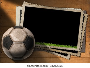 A stack of vintage and blank photo frames with an old soccer ball (football). On a wooden background