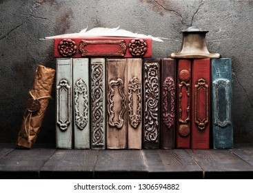 Stack vintage books on a wooden shelf,inkwell and feather.  Retro still life