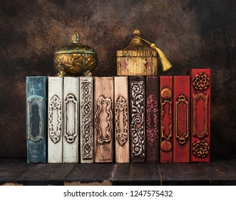 Stack vintage old books and caskets on the shelf. Retro still life
