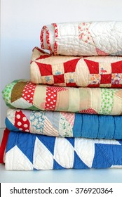 A stack of vintage patchwork quilts