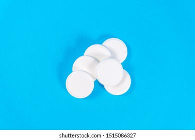 A stack of vitamin and mineral Supplement effervescent tablets isolated on a blue background. Lots of big soluble round tablets for sore throats, colds, fever and headaches. copy space
