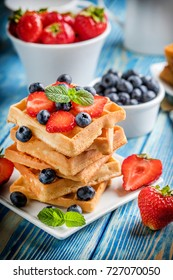 Stack of waffles with fruit on a plate. Small depth of field.