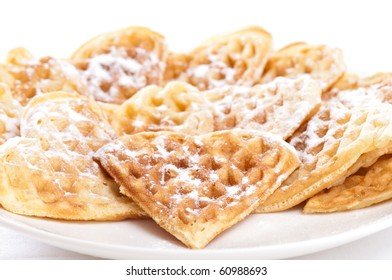 Stack of waffles in shape of heart with powdered sugar on plate