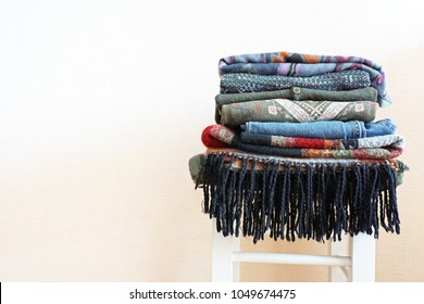 Stack of warm clothes of different patterned fabrics in boho style on a white chair. Empty space.