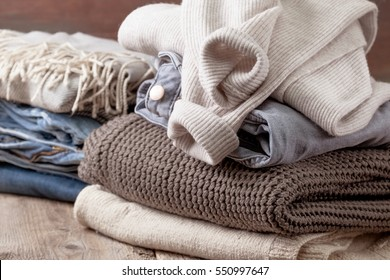 stack of of warm clothes, stack of jeans  on the old wooden background